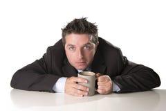 Dedichi l'uomo d'affari in vestito e leghi la tenuta della tazza di caffè come maniaco nella dipendenza della caffeina fotografia stock