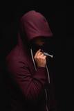 Dedichi l'uomo in un cappuccio con una siringa piena di eroina liquida rossa su un fondo nero Droghe e concetto di dipendenza fotografia stock