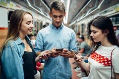 Dedichi la gioventù facendo uso dei telefoni in metropolitana, dipendenza immagini stock libere da diritti
