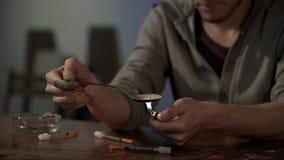 Dedichi preparare la dose di farmaco per l'iniezione, scaldante l'eroina sul cucchiaio, fine immagine stock
