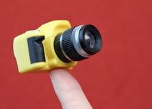 Dedo índice que sostiene una pequeña cámara fotos de archivo libres de regalías