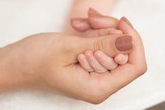 Dedo adulto conmovedor de la mano del bebé Foto de archivo