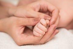 Dedo adulto conmovedor de la mano del bebé Fotos de archivo libres de regalías