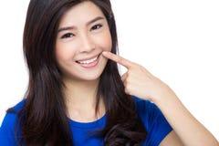 Dedo asiático da mulher que aponta a seus dentes fotos de stock