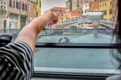 Dedo da hora do ponto da menina na ponte em Veneza fotos de stock