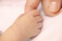 Dedo de la madre de la explotación agrícola de la mano del bebé Foto de archivo libre de regalías