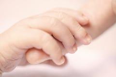 Dedo de la madre de la explotación agrícola de la mano del bebé Imágenes de archivo libres de regalías