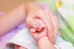 Dedo de la madre del asimiento del bebé en su mano Fotos de archivo libres de regalías