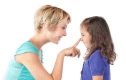 Dedo de la madre en la nariz de la hija Imágenes de archivo libres de regalías