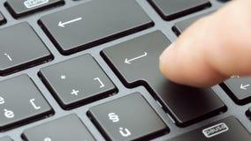 Dedo do close up que pressiona a tecla enter na metragem moderna 4k do teclado do portátil filme