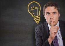 Dedo do homem de negócio na boca contra a parede cinzenta com o gráfico amarelo da ampola Imagens de Stock