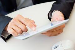 Dedo do homem de negócios que aponta à tela de uma tabuleta digital Imagens de Stock