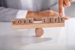 Dedo do ` s do empresário que mostra o desequilíbrio entre o trabalho e a vida imagens de stock