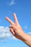 Dedo dos de la mano humana en el cielo azul Foto de archivo libre de regalías