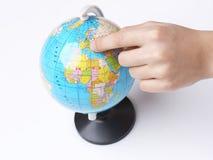 Dedo dos meninos que aponta no globo do mundo Fotos de Stock Royalty Free