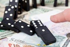 Dedo en dominós en billetes de banco Imagen de archivo libre de regalías