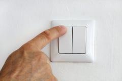 Dedo en el interruptor de la luz eléctrica fotos de archivo