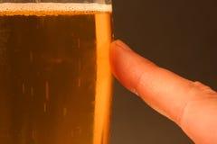 Dedo en la cerveza - serie foto de archivo