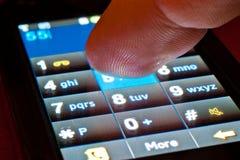 Dedo en smartphone Foto de archivo