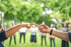 Dedo indicador do toque do homem e da mulher junto no jardim com os outros povos do borrão no fundo fotos de stock royalty free