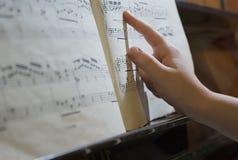 Dedo na folha de música Imagem de Stock