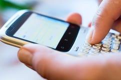 Dedo no smartphone qwerty Fotografia de Stock