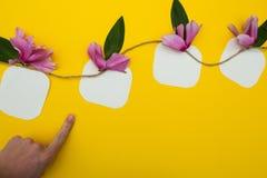 Dedo que aponta à nota na corda com flores em um fundo amarelo, com espaço para o texto imagem de stock