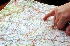 Dedo que aponta o mapa do curso da navegação Fotos de Stock Royalty Free