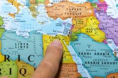 Dedo que aponta a um mapa colorido do pa?s de Egito no Norte de ?frica em ingl?s e em franc?s fotografia de stock