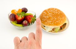 Dedo que escolhe entre o Hamburger e os frutos. imagens de stock royalty free