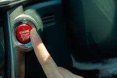 Dedo que pressiona o botão de parada do começo do motor imagens de stock