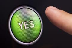 Dedo que pressiona um botão verde do YES no écran sensível Foto de Stock