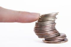 dedo que utiliza la columna de monedas Imagen de archivo libre de regalías