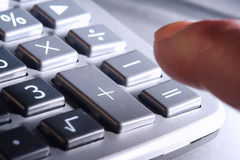Dedo sobre telclado numérico de la calculadora más y signos de igualdad Fotos de archivo libres de regalías