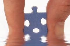 Dedo y rompecabezas en agua imagenes de archivo