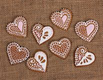 Dedorated h, de,eart gingerbread cookies. Baked heart shape gingerbread cookies on burlap background royalty free stock image