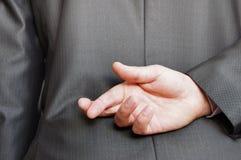 Dedos cruzados detrás de una parte trasera adecuada Imagen de archivo