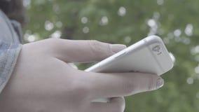 Dedos da jovem mulher que datilografam em seu smartphone filme