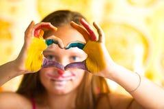 Dedos da menina dobrados sob a forma do coração Fotografia de Stock Royalty Free