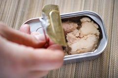 Dedos da pessoa que abrem a lata de lata com fígado de bacalhau Imagem de Stock