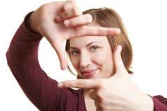 Dedos da terra arrendada da mulher como um frame Fotos de Stock Royalty Free