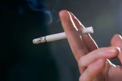 Dedos de la mujer con el cigarrillo que fuma Imagenes de archivo