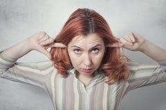Dedos de la mujer joven en los oídos que no escuchan Foto de archivo libre de regalías