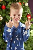 Dedos de la travesía del muchacho delante del árbol de navidad Imagen de archivo