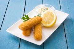 dedos de peixes fritados friáveis com limão e molho na madeira azul Foto de Stock Royalty Free