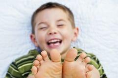 Dedos del pie de los pies desnudos de la cara del niño del muchacho Imagen de archivo libre de regalías