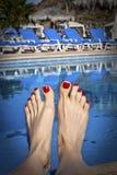 Dedos del pie pintados en la piscina Foto de archivo libre de regalías
