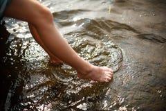 Dedos del pie que sumergen en agua Fotografía de archivo