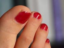 Dedos del pie rojos de los clavos fotografía de archivo