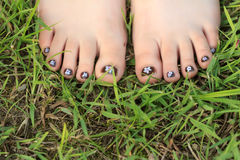 Dedos do pé da menina com arte feito a mão criançola do prego fotografia de stock royalty free